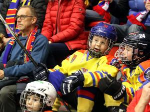 Malí hokejisté čekající na svůj čas na ledě zatím mezi diváky